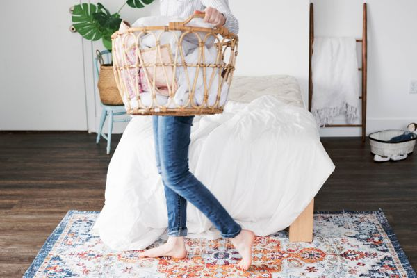 person picking up clutter around the bedroom