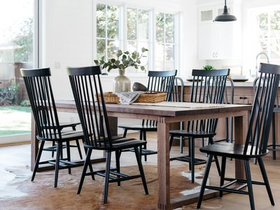 Farmhouse style dining table with black chairs and wooden table