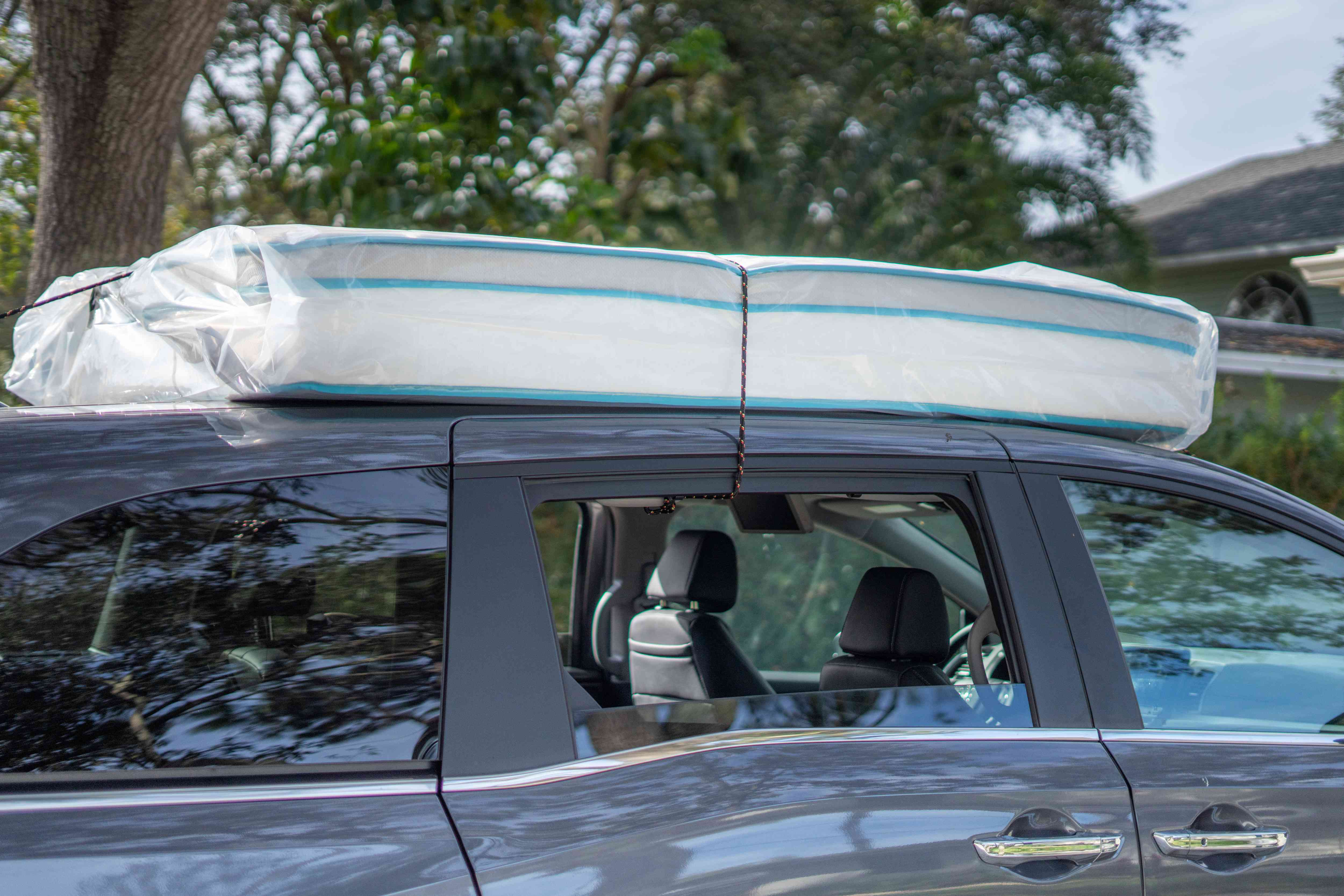 open windows to further secure the mattress to the roof of the car