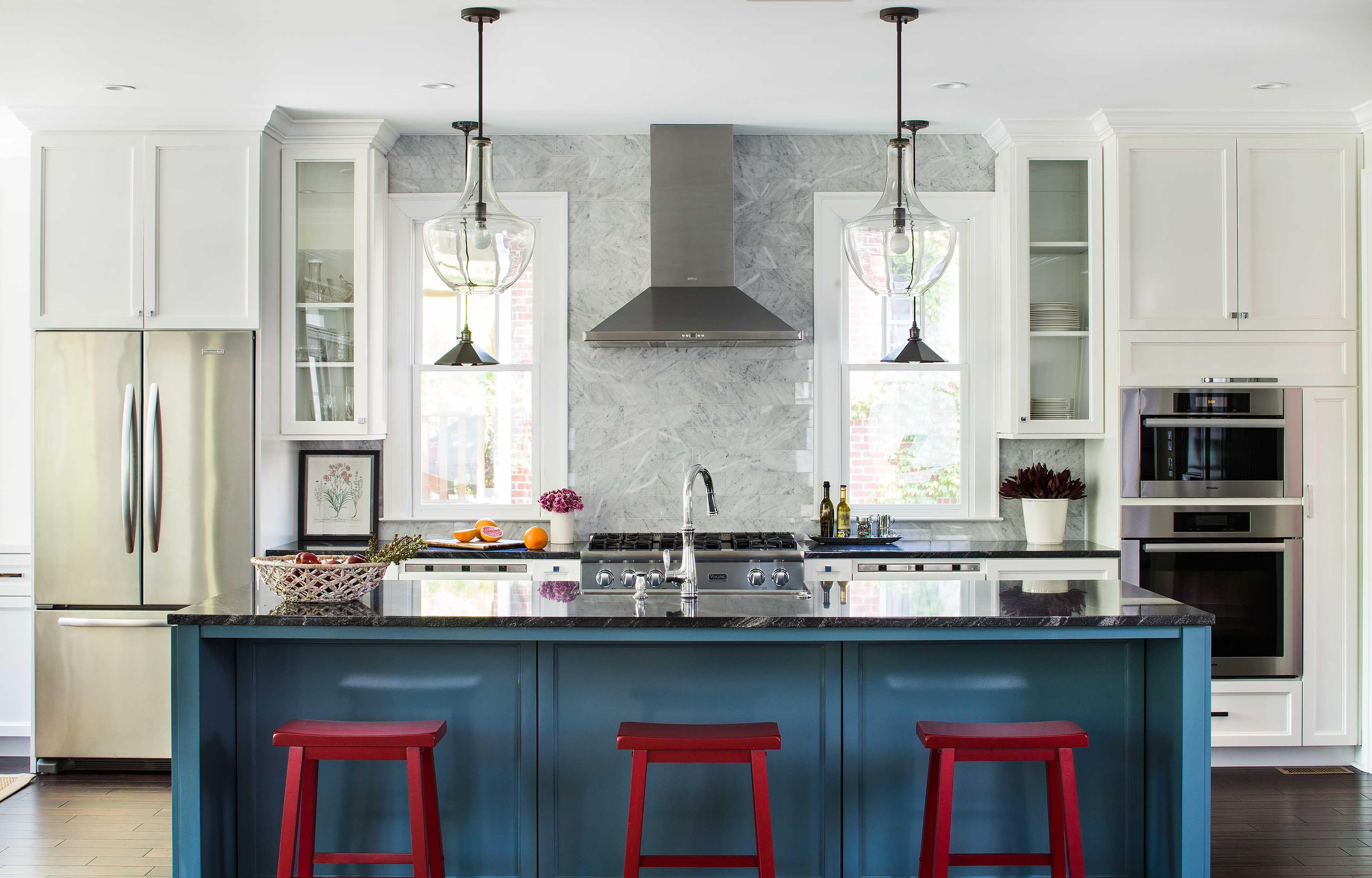 Cocina blanca con gabinetes azules y tres taburetes rojos