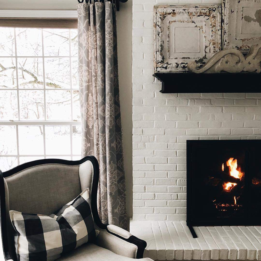 Vintage tiles on a mantle above a fireplace.