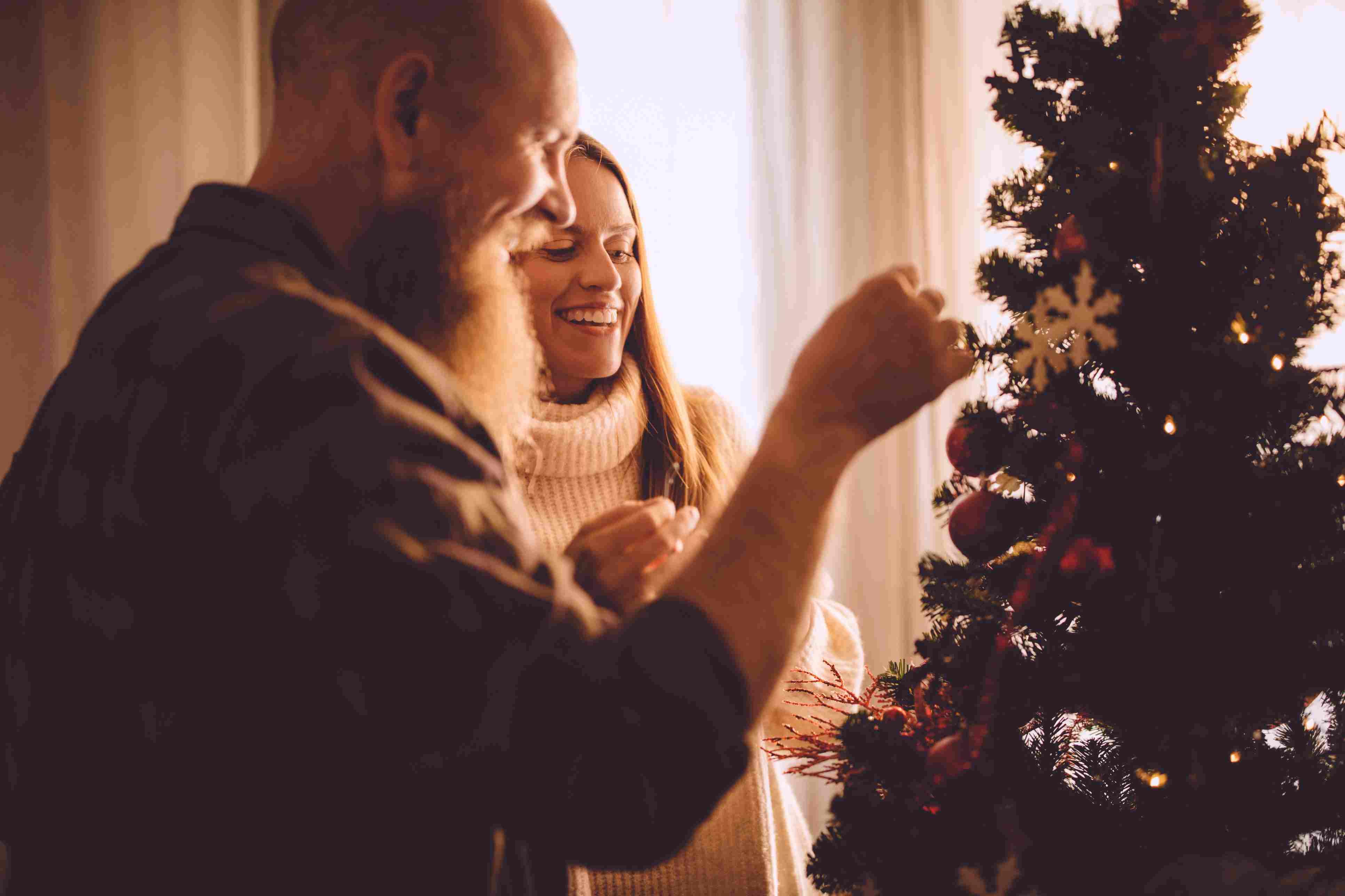 Romántica pareja madura decorando el árbol de Navidad en casa