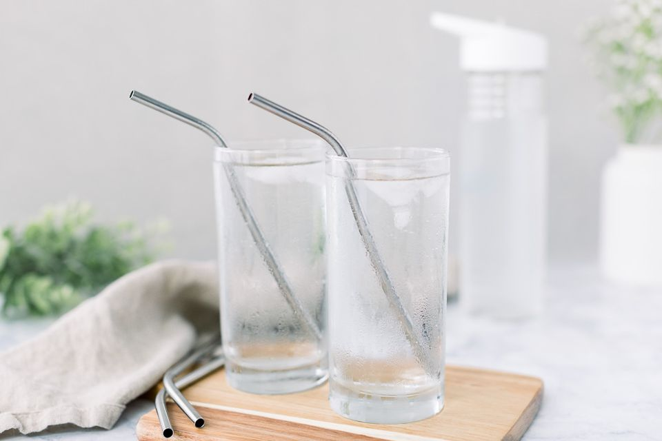 metal straws and water bottle in the background
