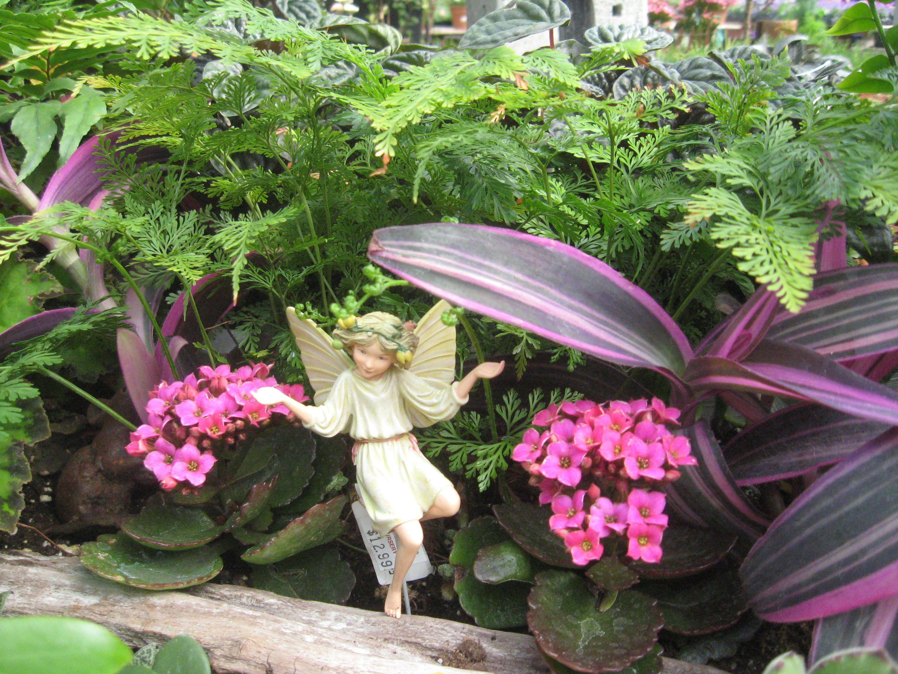 Estatua de hadas entre plantas de jardín rosadas