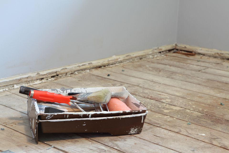 Tools for painting sitting on wooden subfloor in front of dirty walls ready to be painted.