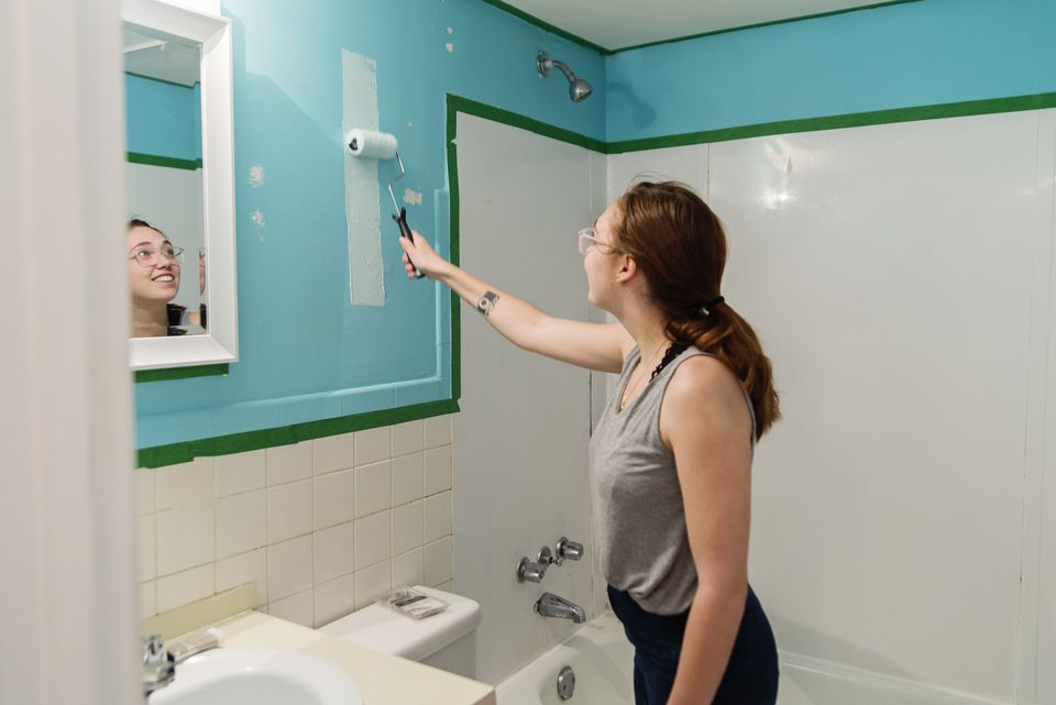 Young girl painting bathroom blue