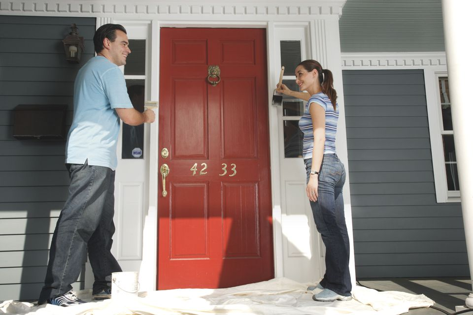 Couple painting doorframe on front door of house