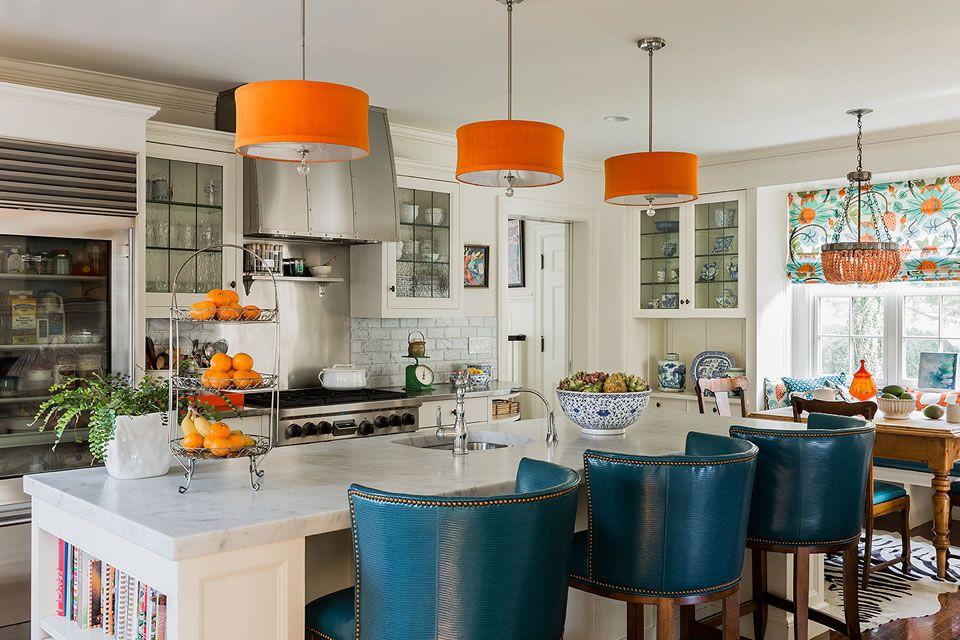 Luces colgantes naranjas, sillas azules y encimeras blancas en una cocina