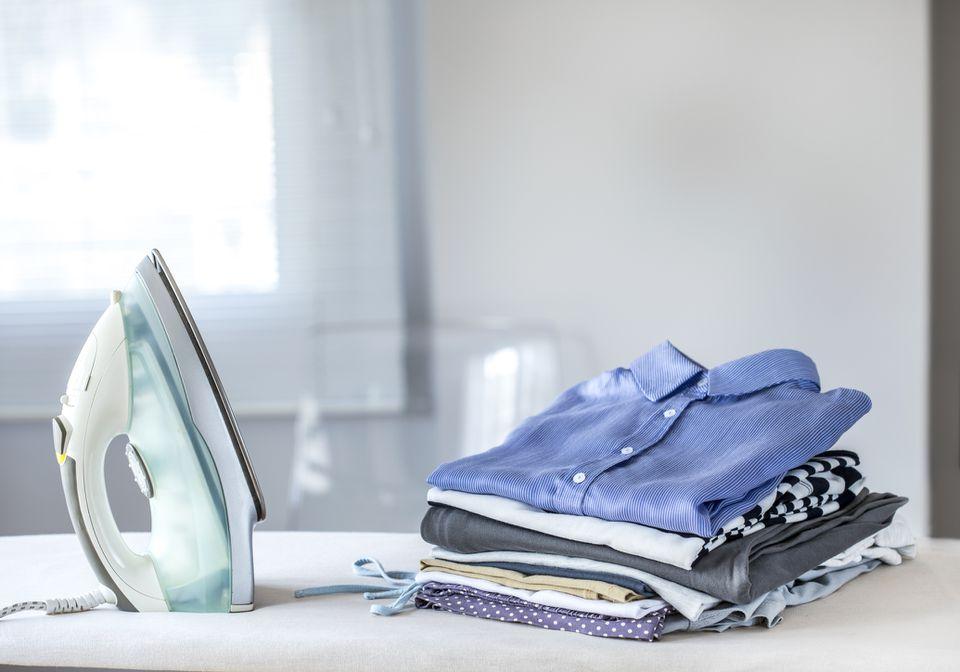 Iron next to folded clothes