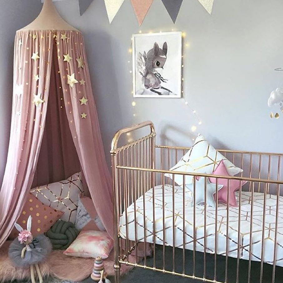 Cozy canopy tent reading corner in pink and grey nursery room