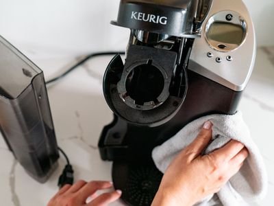 person cleaning a keurig