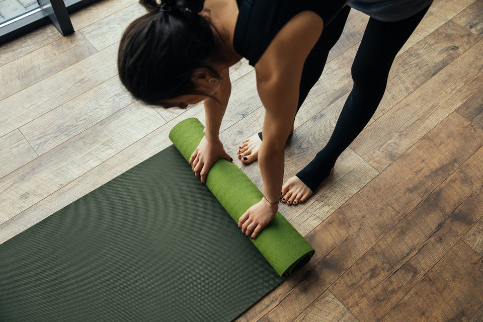 Young woman rolling up yoga mat on wood floor