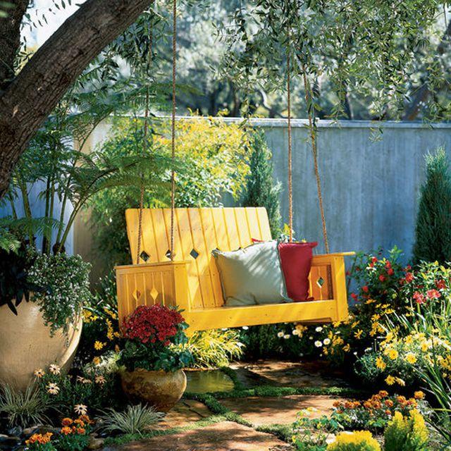 Un columpio de porche amarillo en un jardín
