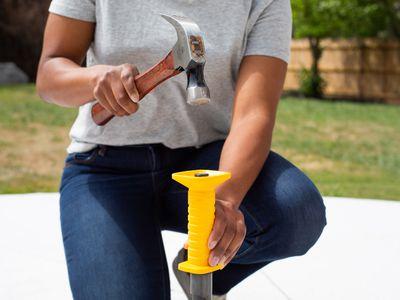 Hammer driving in yellow concrete nail gun