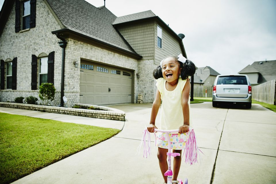 Smiling young girl riding scooter in driveway