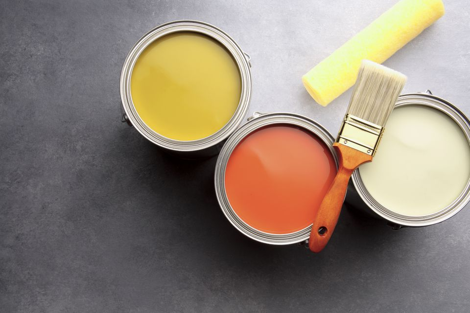 Cans of yellow and orange paint shot from overhead