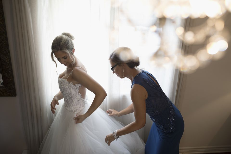 Mother helping bride with gown