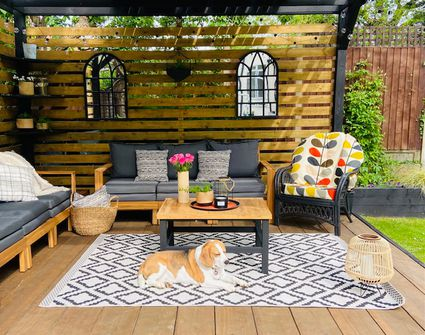 This outdoor patio features a privacy wall, mirrors, a rug, cozy textures, and bright pops of color