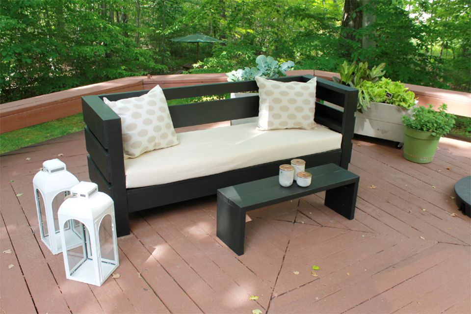 A black sofa and coffee table on a deck