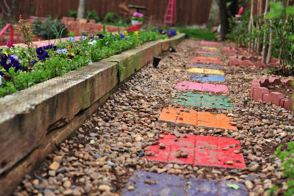 Colorful stepping stones on a gravel walkway surrounded by flowers.