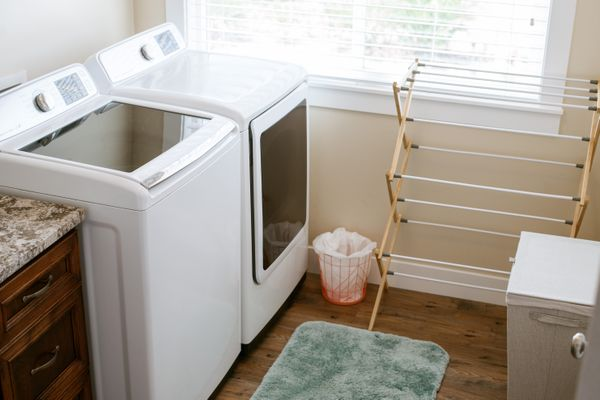 Laundry room with drying rack and white machines near brightly-lit window