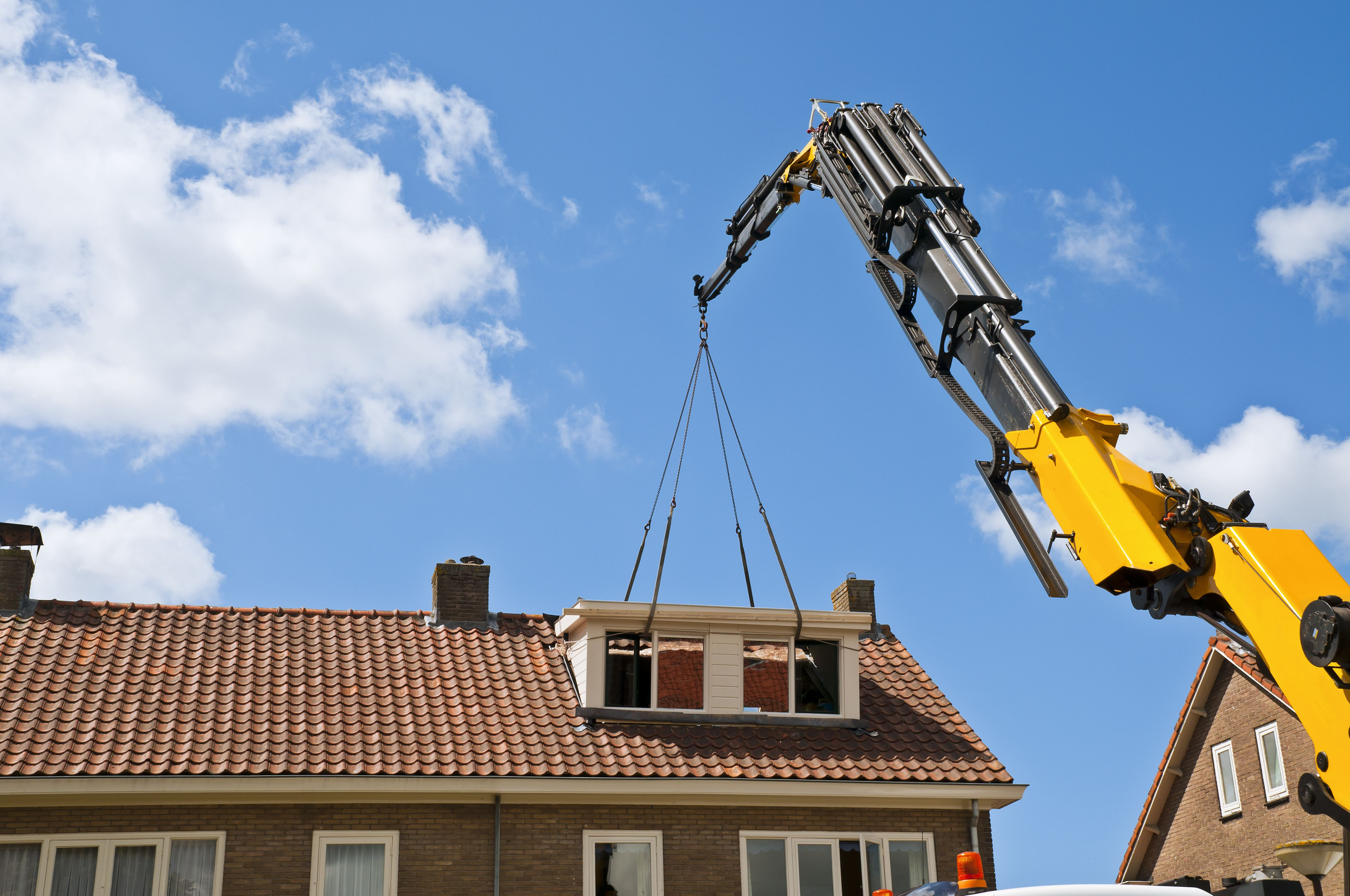 A prefab dormer is installed with a crane
