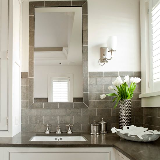 Grey and white bathroom facing mirror above sink.