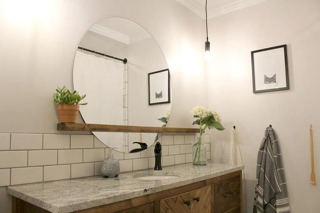 Un espejo flotante y estante en un baño