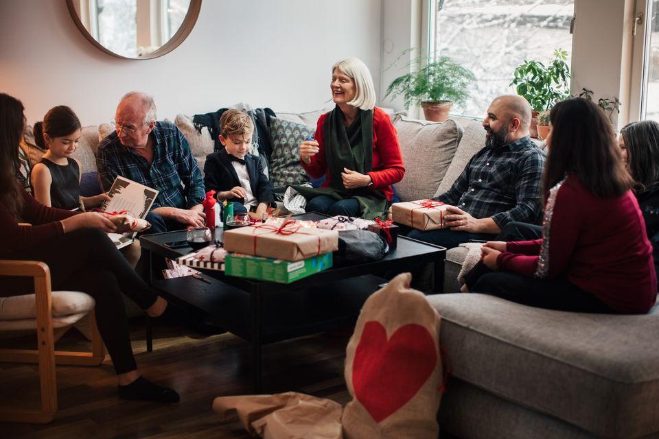 Niño mostrando regalos de Navidad a la familia de varias generaciones en la sala de estar