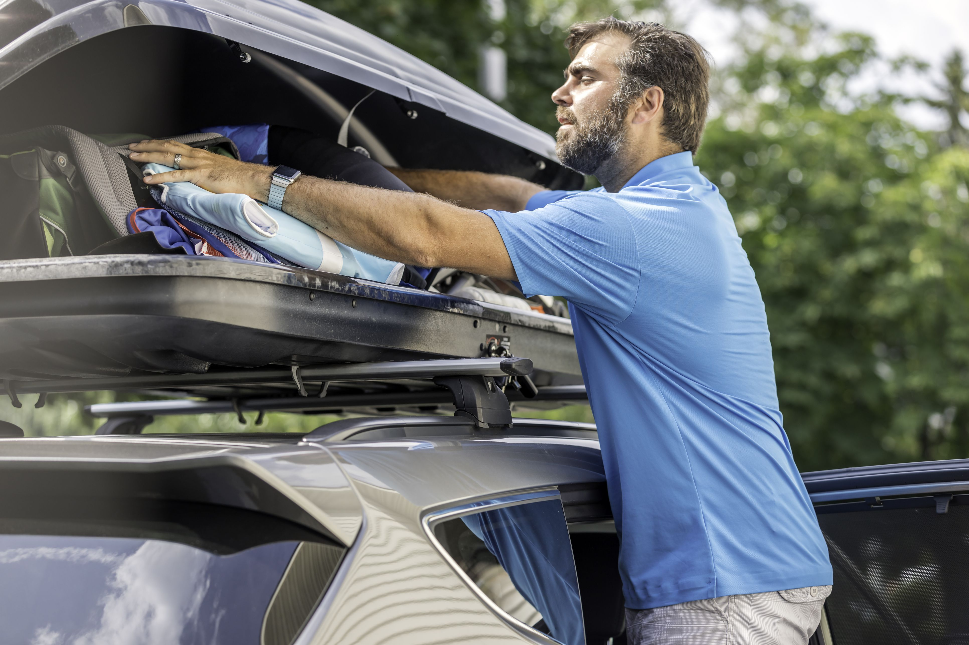 Men Filling Cargo Box Container on Roof Rack for Vacations or Camping