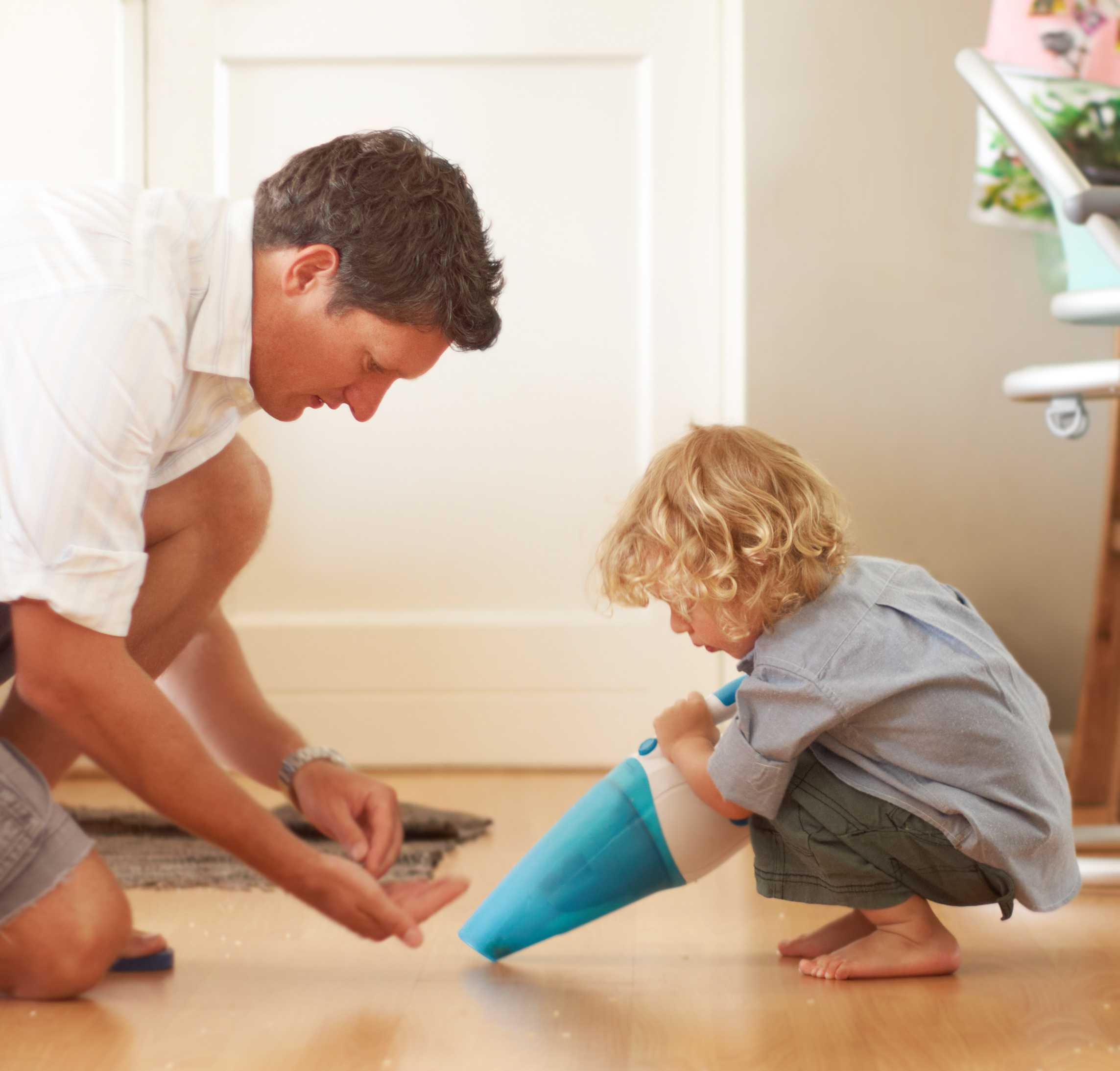 dad and kid using a dustbuster