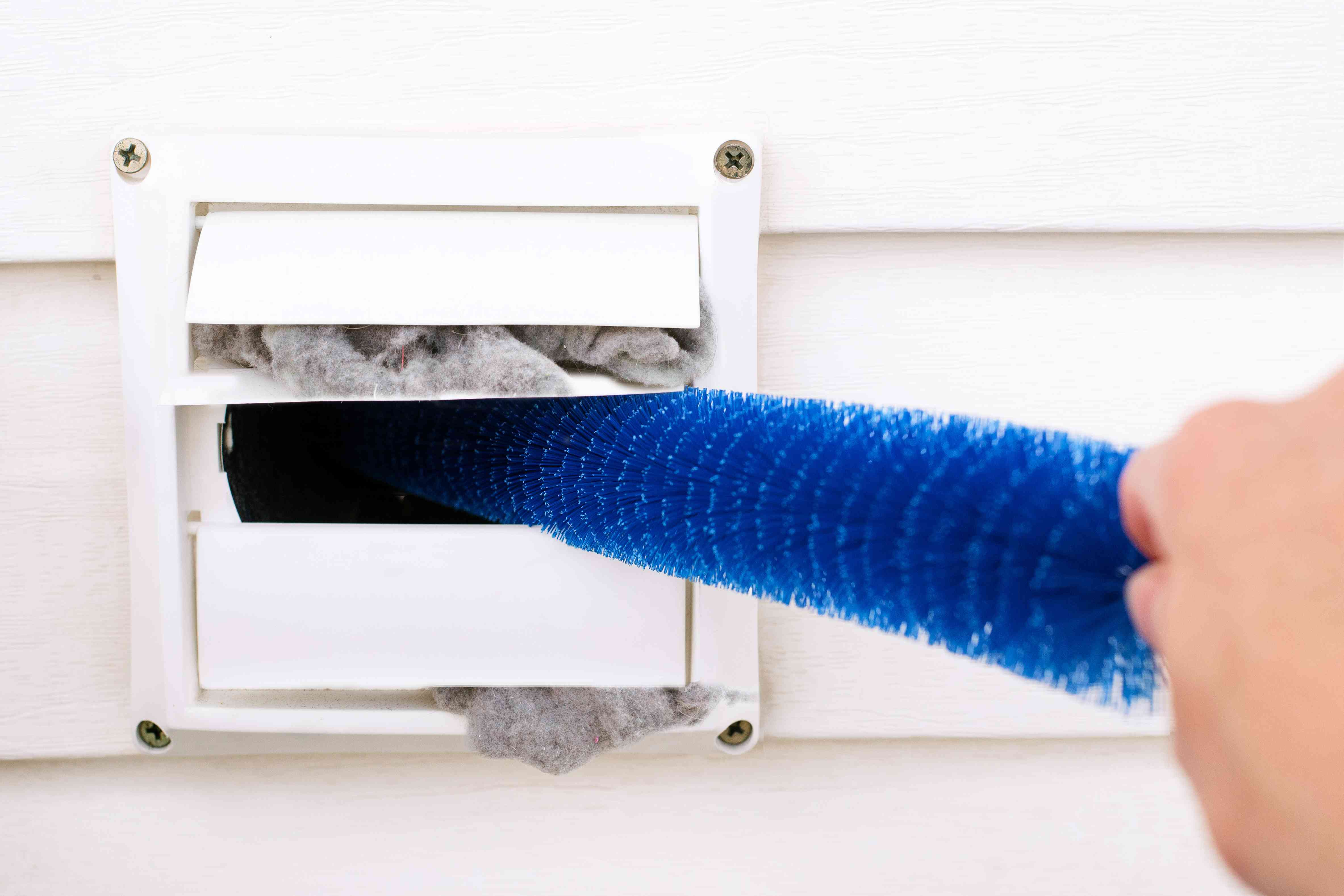 Long lint brush removing lint and debris from outside dryer vent