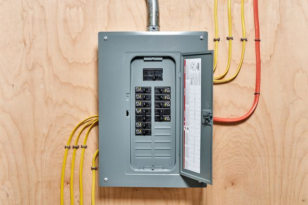 Electrical circuit breaker panel with door open and yellow and orange wires connected behind