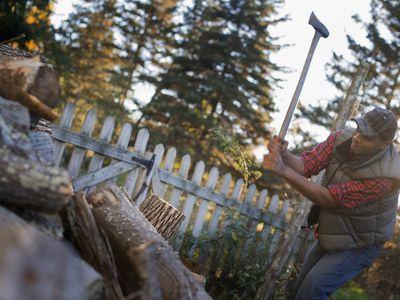 A man wielding an axe, and chopping wood, splitting logs for the fire.