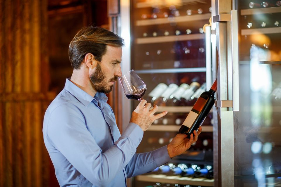 man tasting wine from fridge