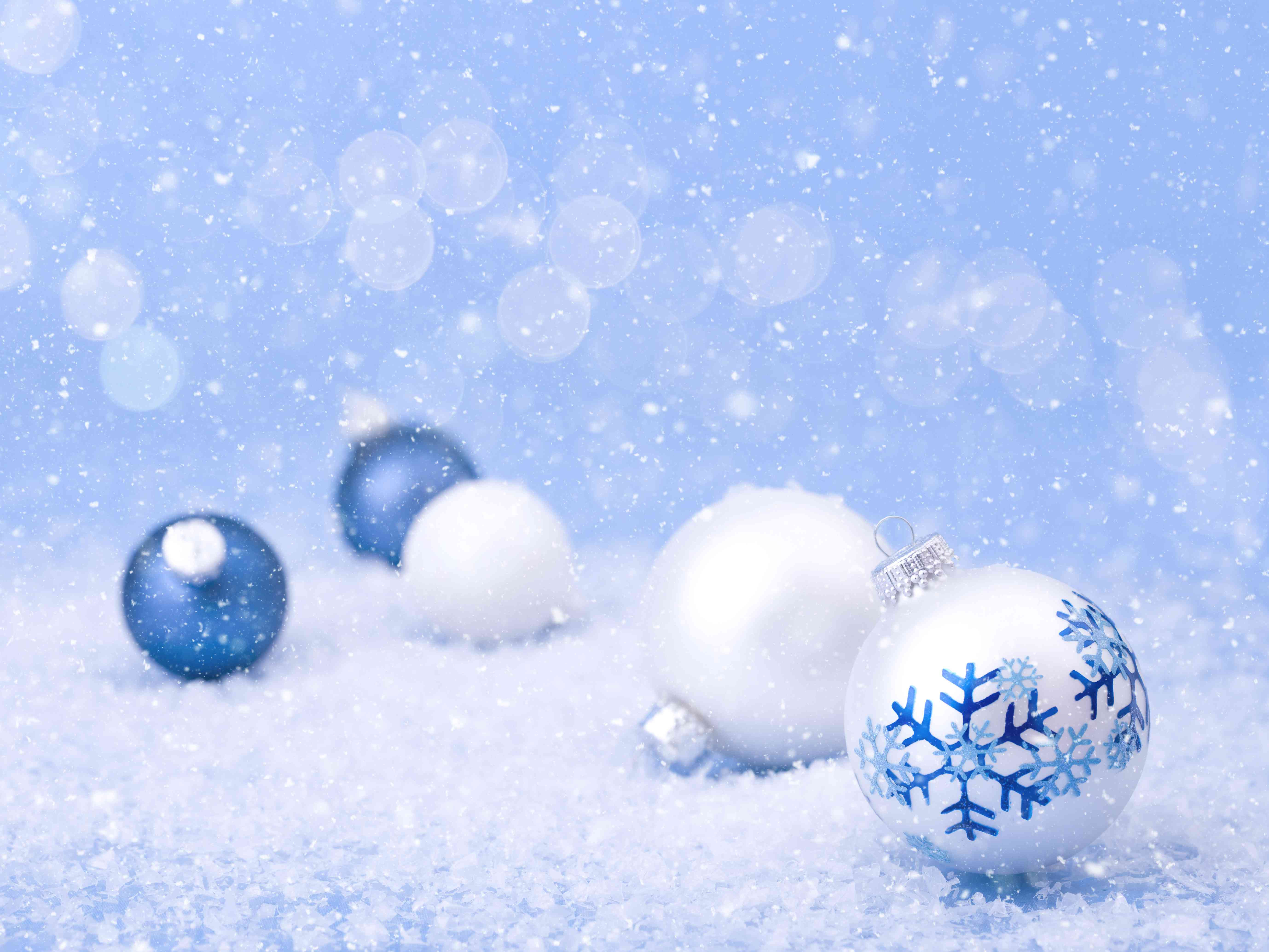 Christmas holiday blue and white snowflake themed baubles with snow and defocused lights
