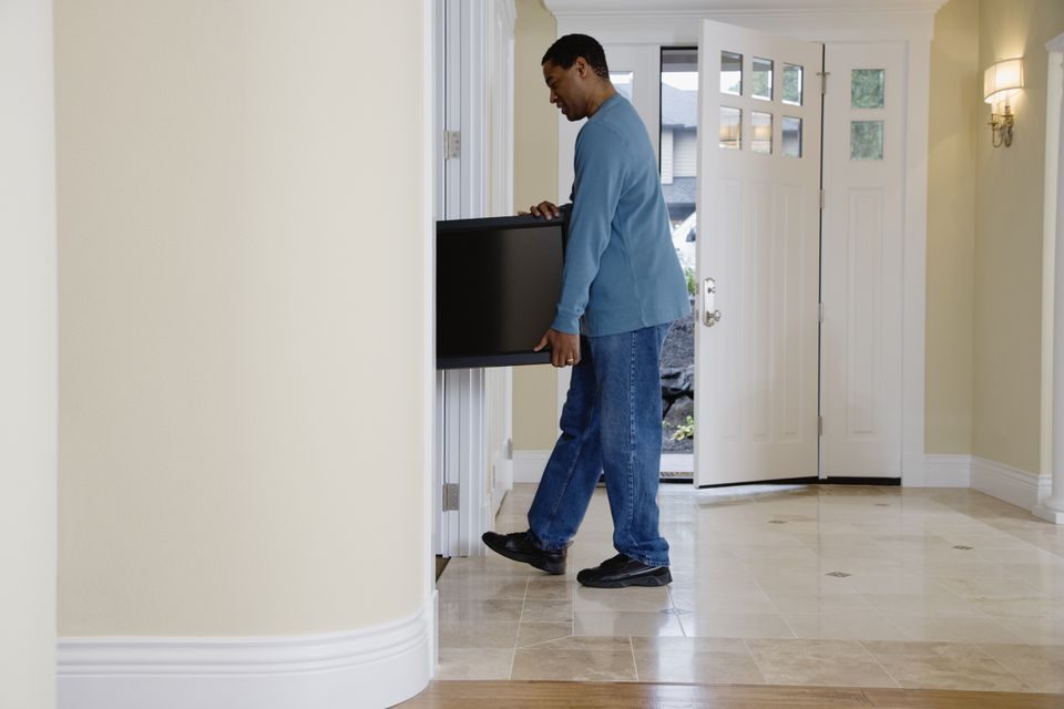 Man moving flat screen TV through doorway