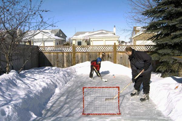 Father and Son Playing Hockey in Backyard, Winnipeg, Manitoba