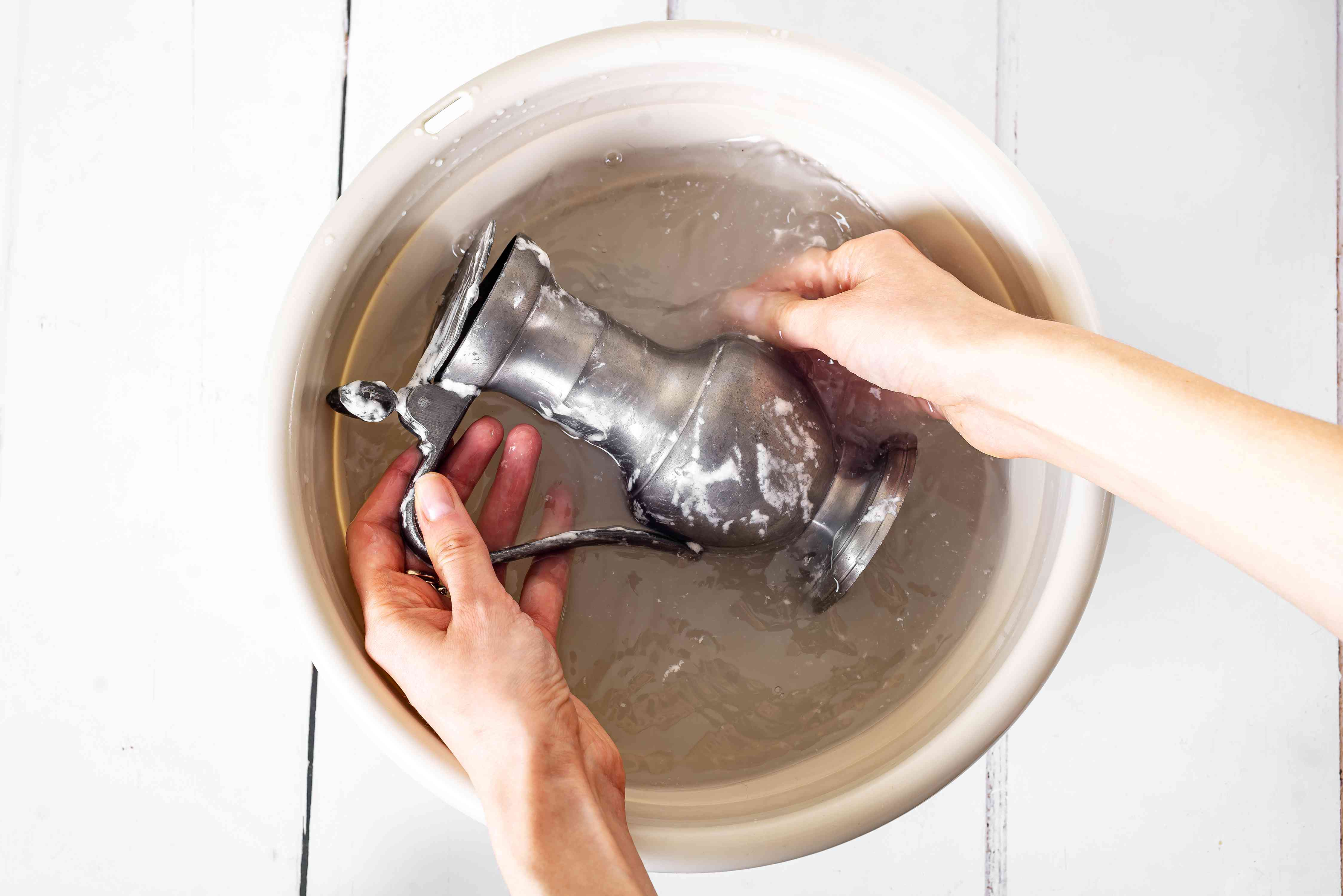 Pewter dispenser rinsed in bucket with clean water