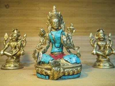 Tibetan brass and stone statue of Green Tara close-up
