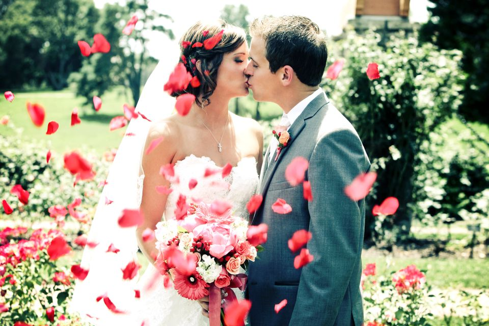 Bride and groom kissing surrounded by flower petals