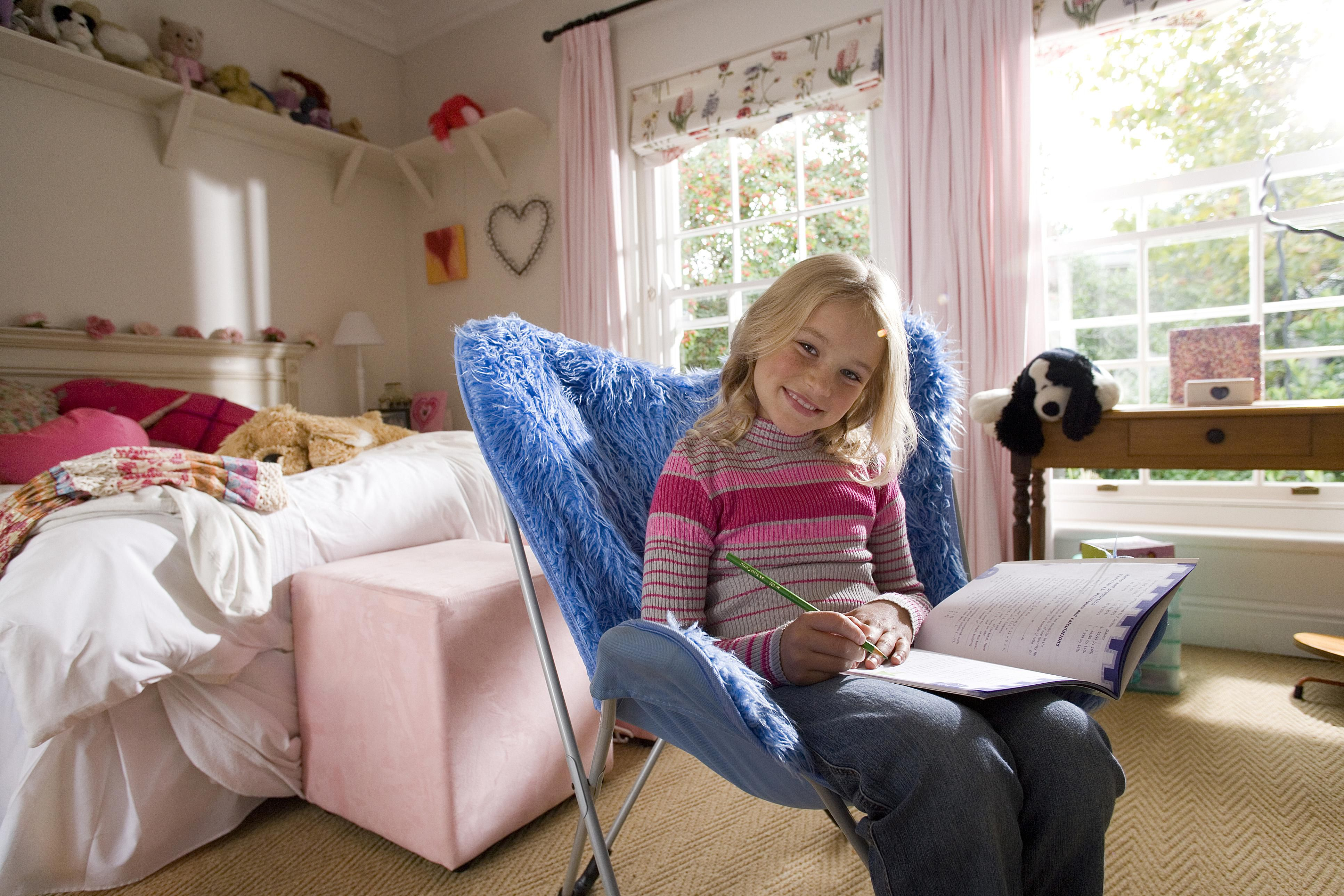 A girl writing in a notebook in her room.