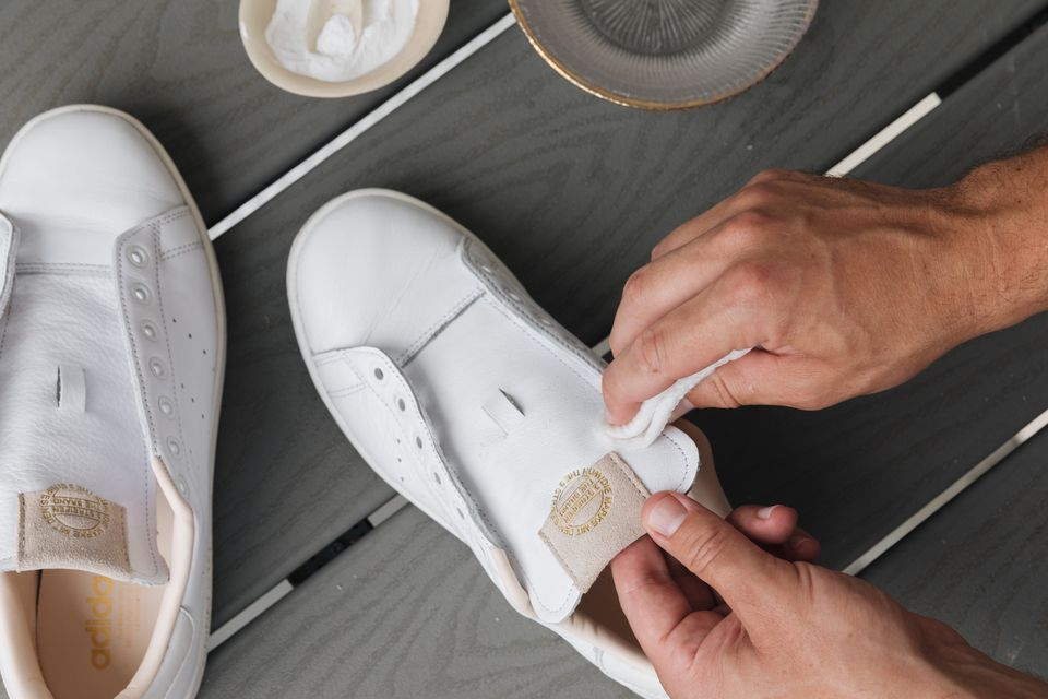 person spot cleaning a white leather shoe