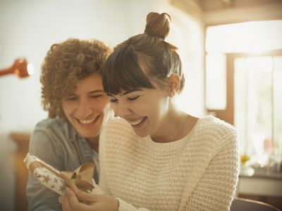 Smiling young couple opening anniversary gift