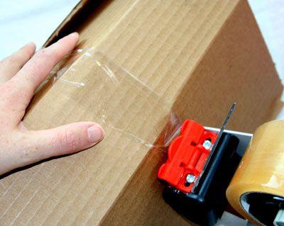 Persona que usa cinta de embalaje para pegar el cartón .