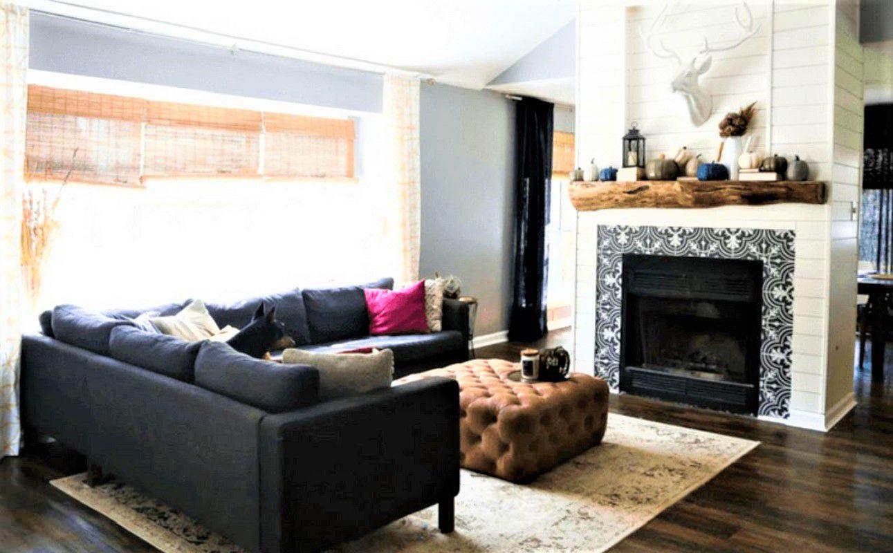Sala de estar con azulejos ornamentados alrededor de la chimenea, sección gris, otomana marrón y alfombra beige después del cambio de imagen