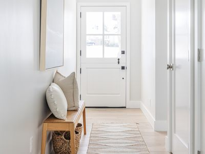 White-walled entry way with wooden bench and white pillows on top