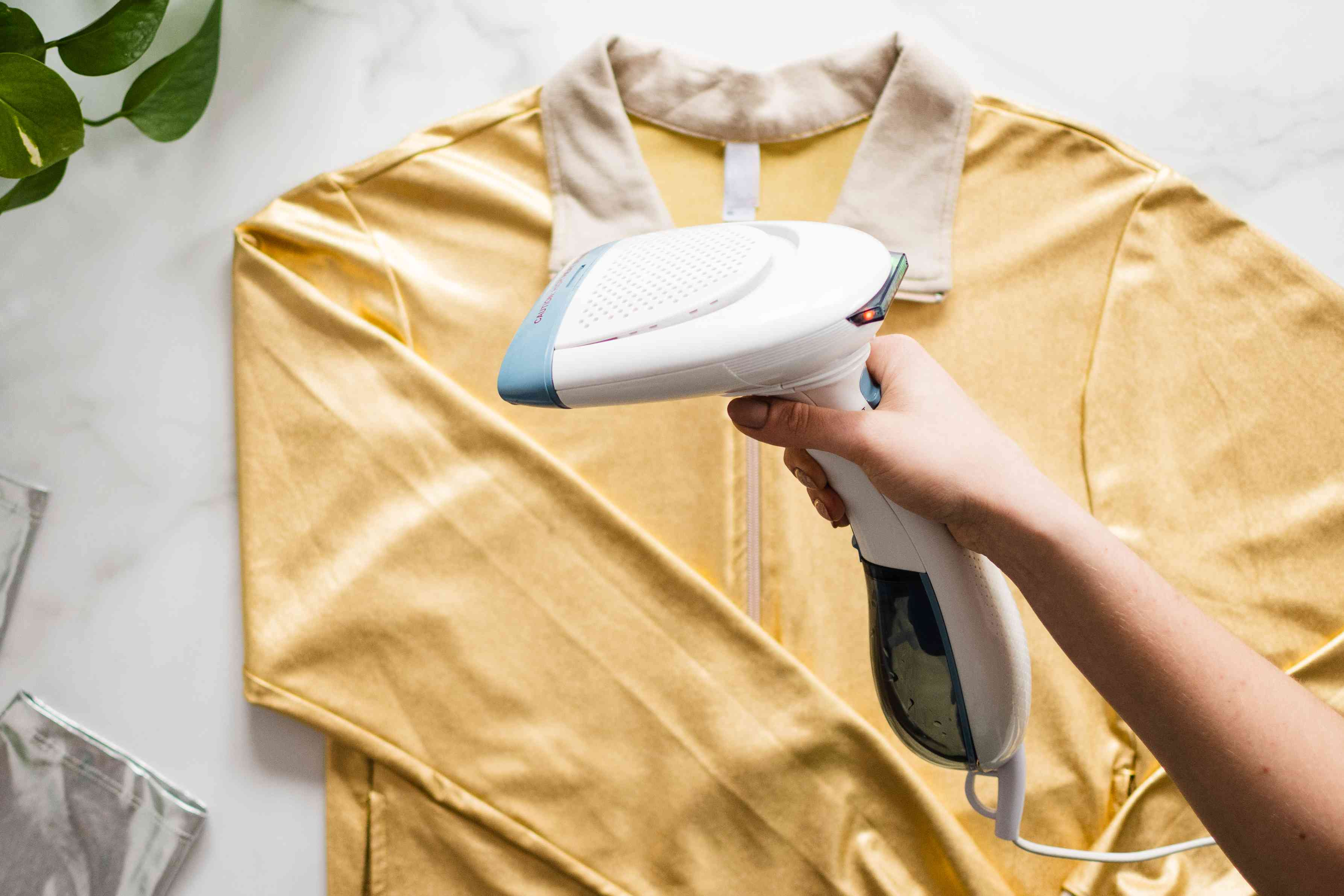Clothes steam passing over yellow metallic jacket to remove wrinkles