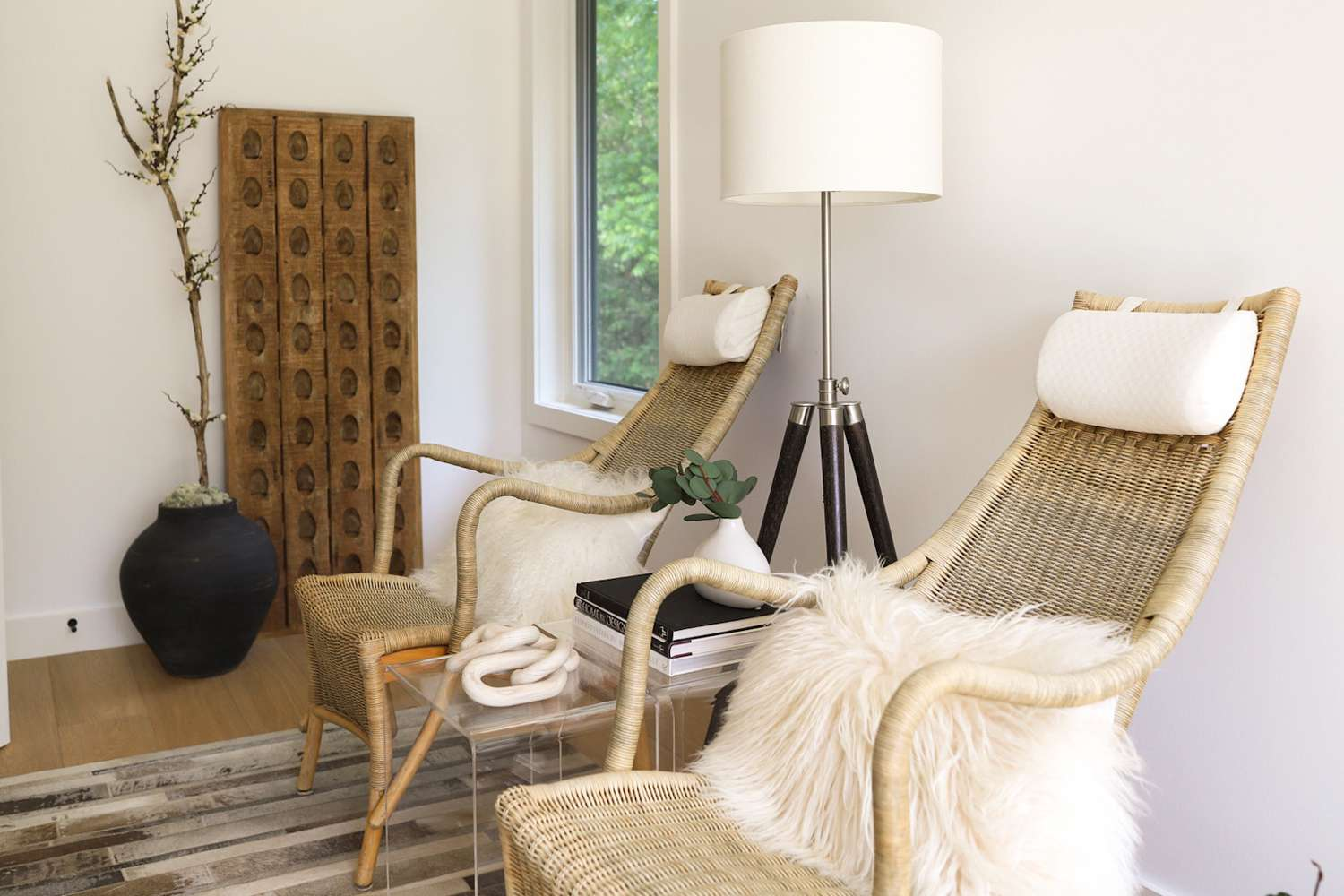 Neutral wooden chairs with faux sheepskin pillows on top next to lamp and side table with books