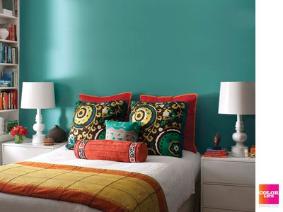 a bed in front of a dark teal accent wall